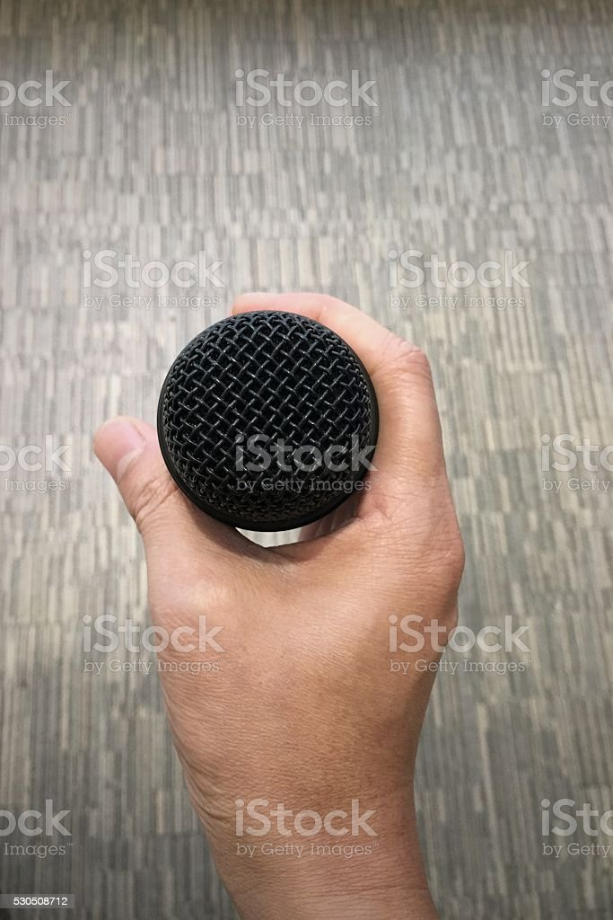 hand holding a microphone stock photo