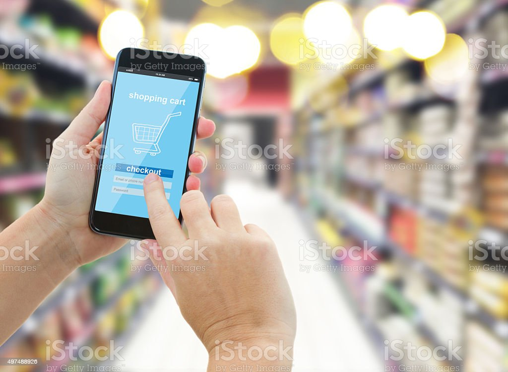 hand holding a modern smartphone in supermarket stock photo