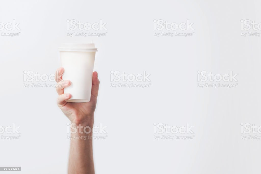 Hand holding a mug with delicious coffee in a cafe on a white background, mock up, blank, your cafe shop design stock photo