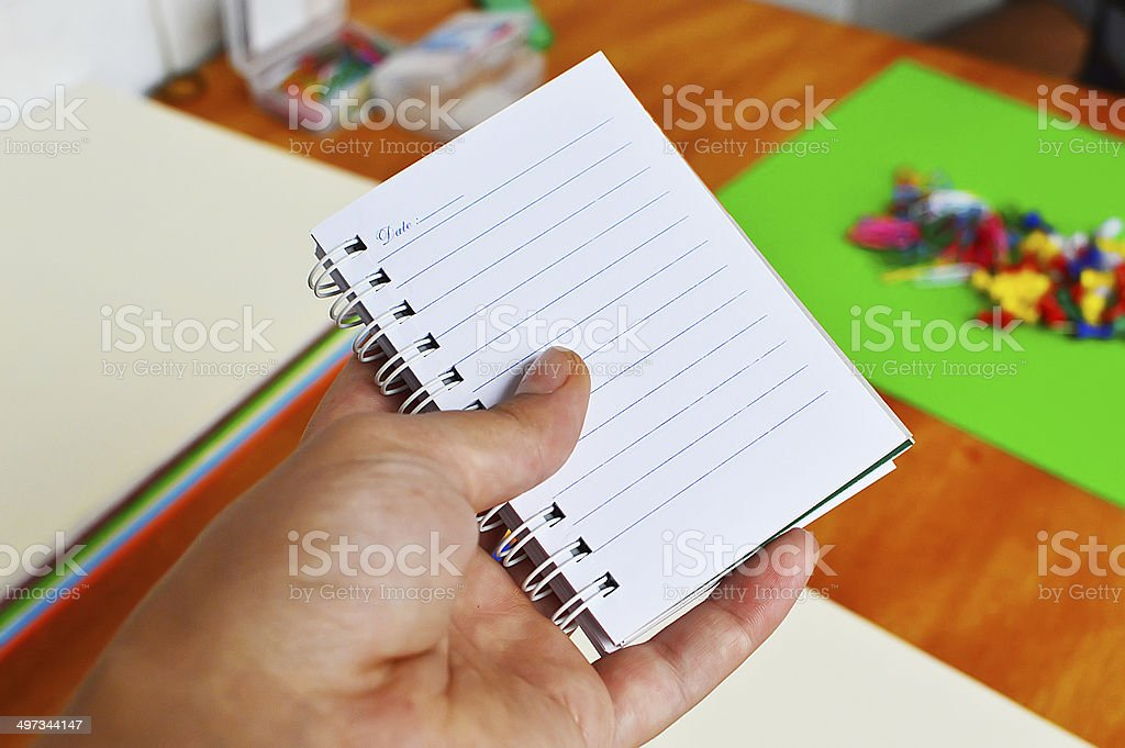 Hand holding a open notebook stock photo