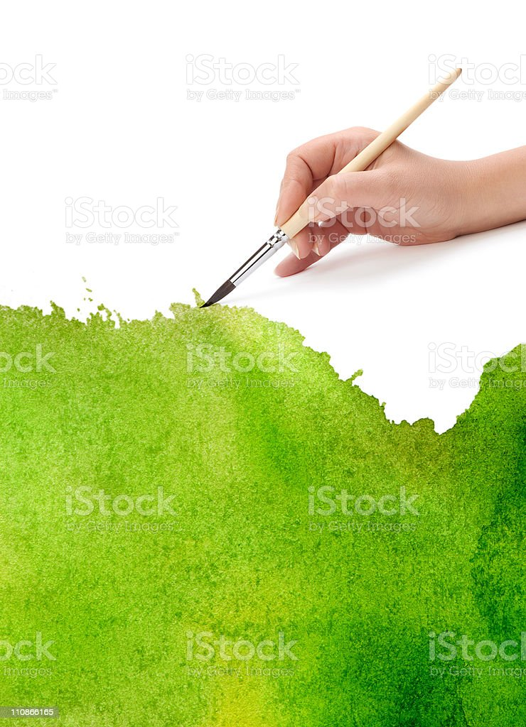 A hand holding a paint brush painting the canvas green stock photo