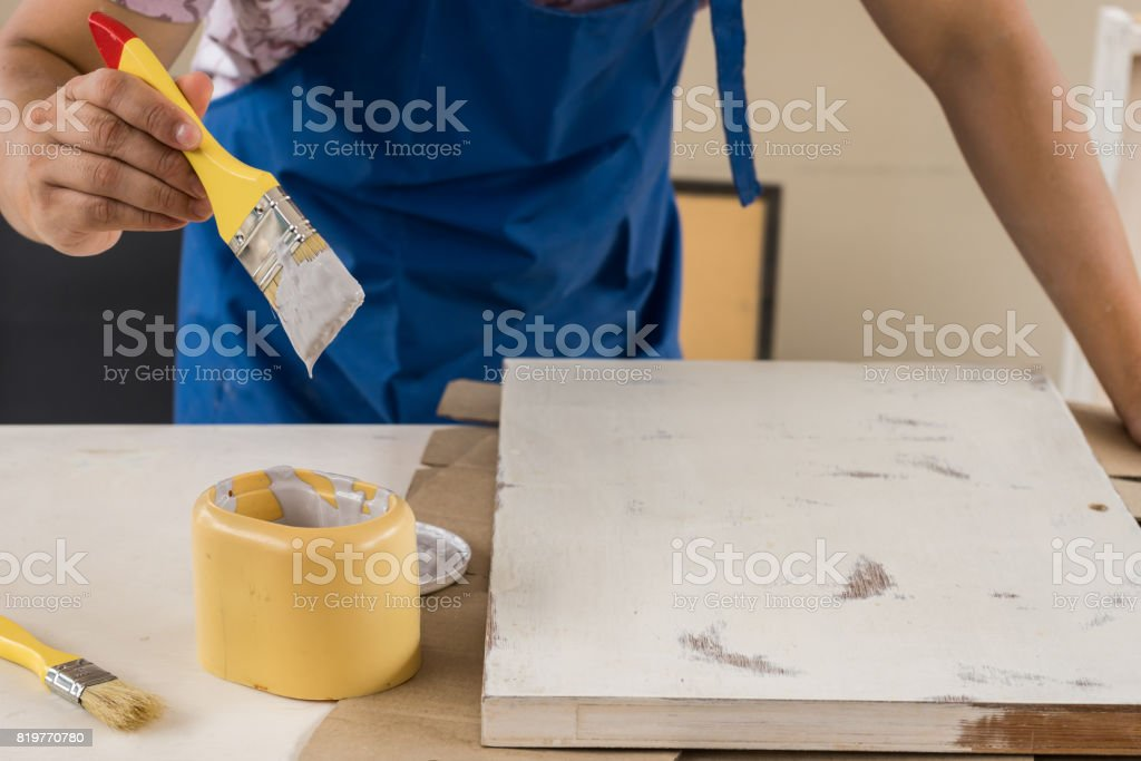 Hand holding a paint brush to paint gray on wood. Renovate old furniture to new repaint stock photo