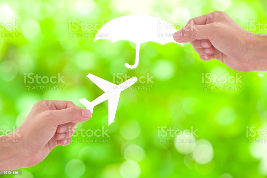 Hand holding a paper airplane and umbrella on green background, Travel Insurance stock photo