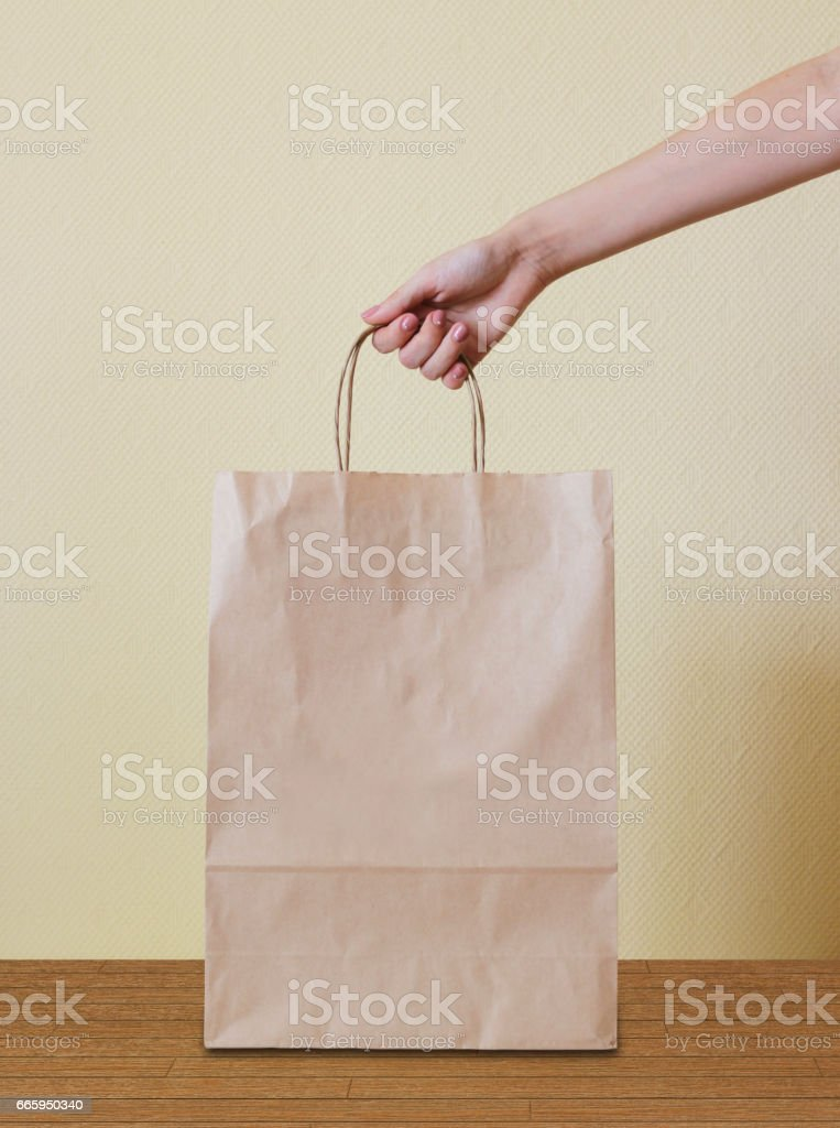 Hand holding a paper bag on wooden floor. stock photo