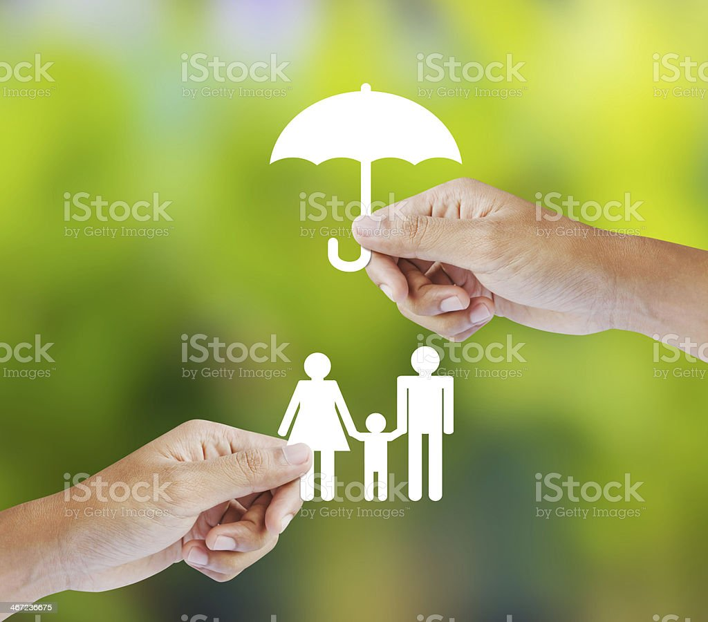 Hand holding a paper family and umbrella on green background stock photo
