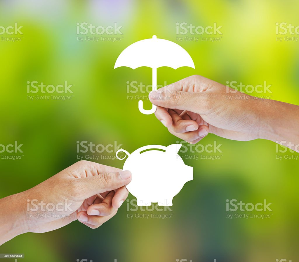 Hand holding a paper  piggy bank and umbrella stock photo