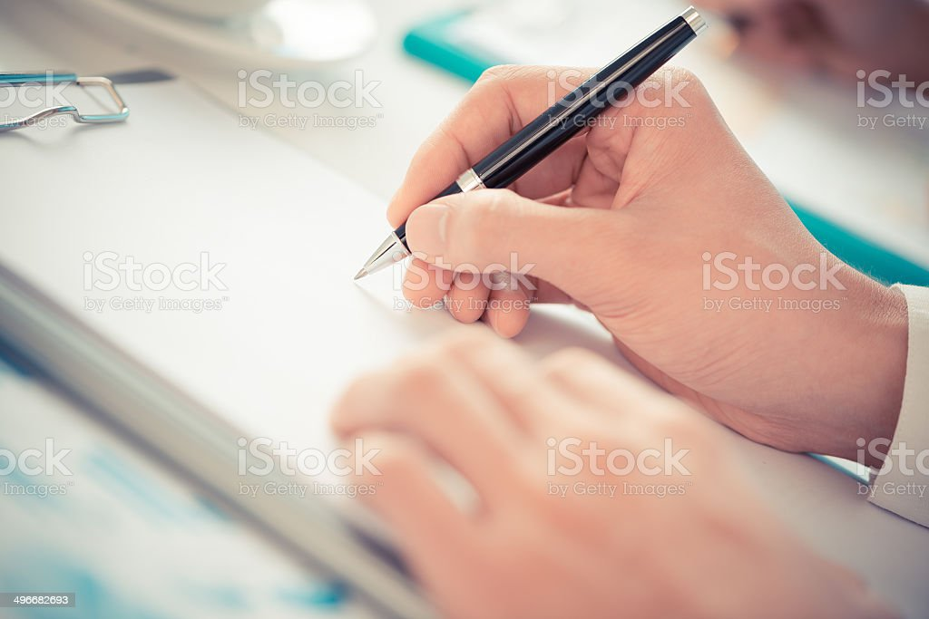 Hand holding a pen on a clipboard stock photo