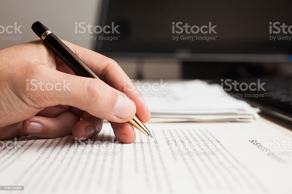 A hand holding a pen on top of a pile of paperwork stock photo