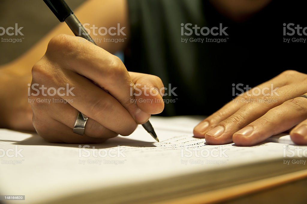 A hand holding a pen writing in a notebook stock photo