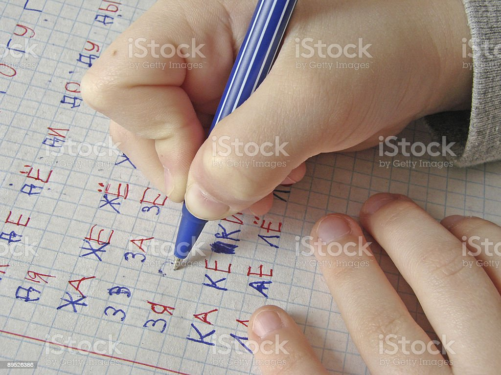 Hand holding a pen writing numbers and letters on paper stock photo