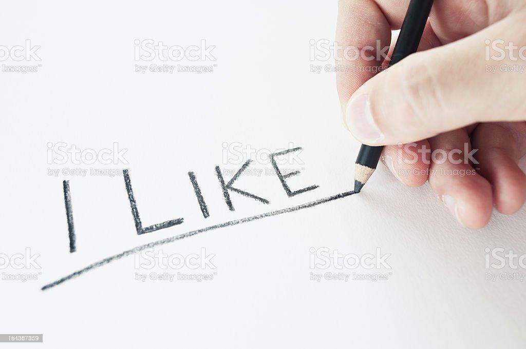 Hand Holding A Pencil Writing I Like royalty-free stock photo