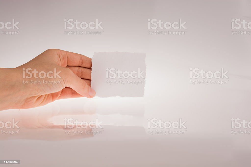 Hand holding a piece of paper stock photo