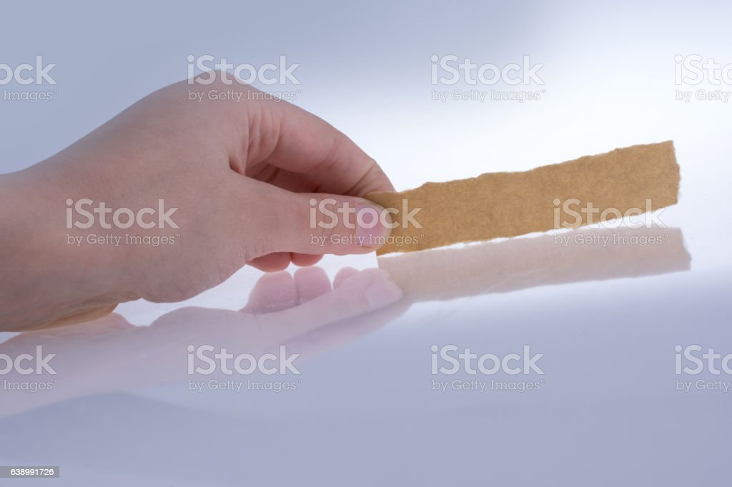 Hand holding a piece of torn paper stock photo