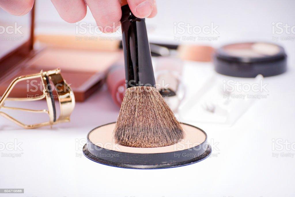 Hand holding a powder brush with cosmetics set stock photo