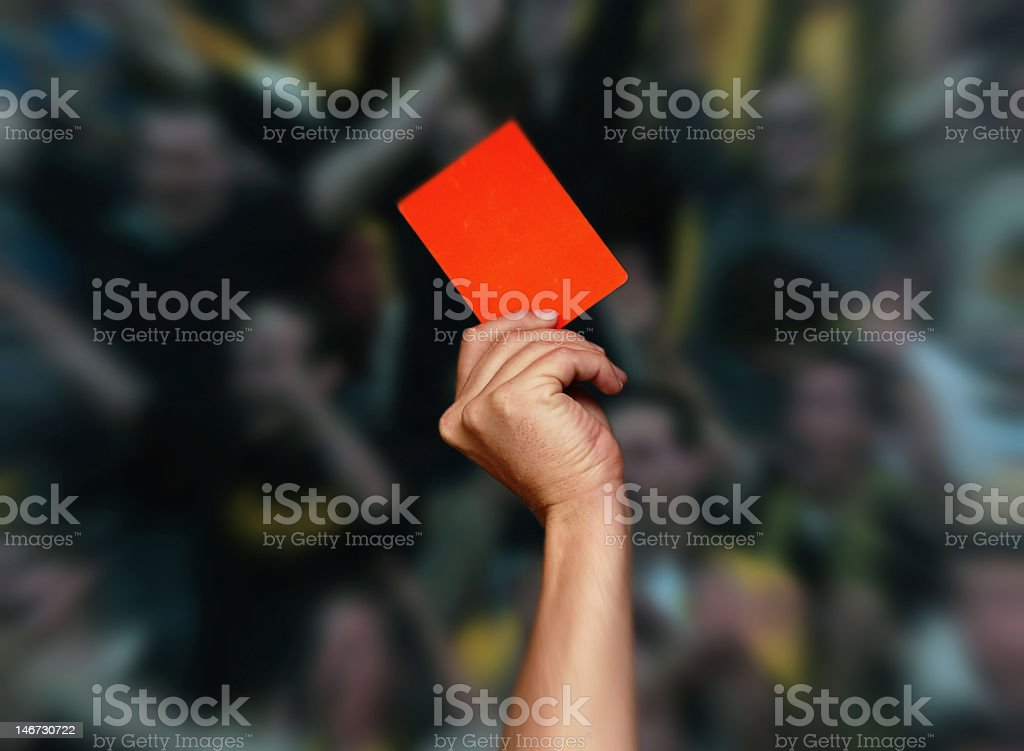 A hand holding a red card up in front of a blurred crowd stock photo