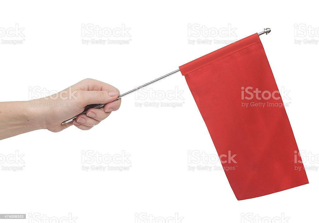 Hand holding a red flag isolated on white background. stock photo