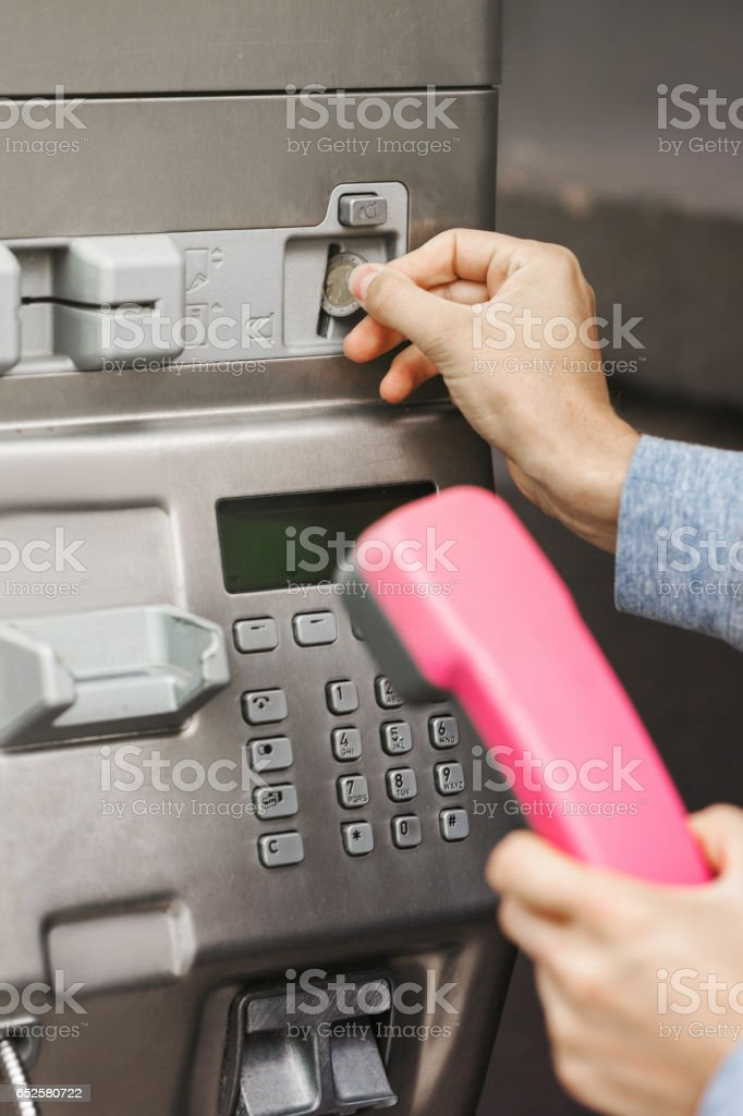 Hand holding a red handset of a public telephone stock photo