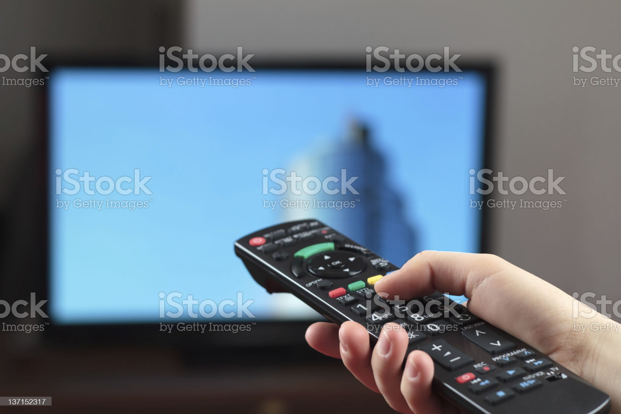 Hand holding a remote control with television in background royalty-free stock photo