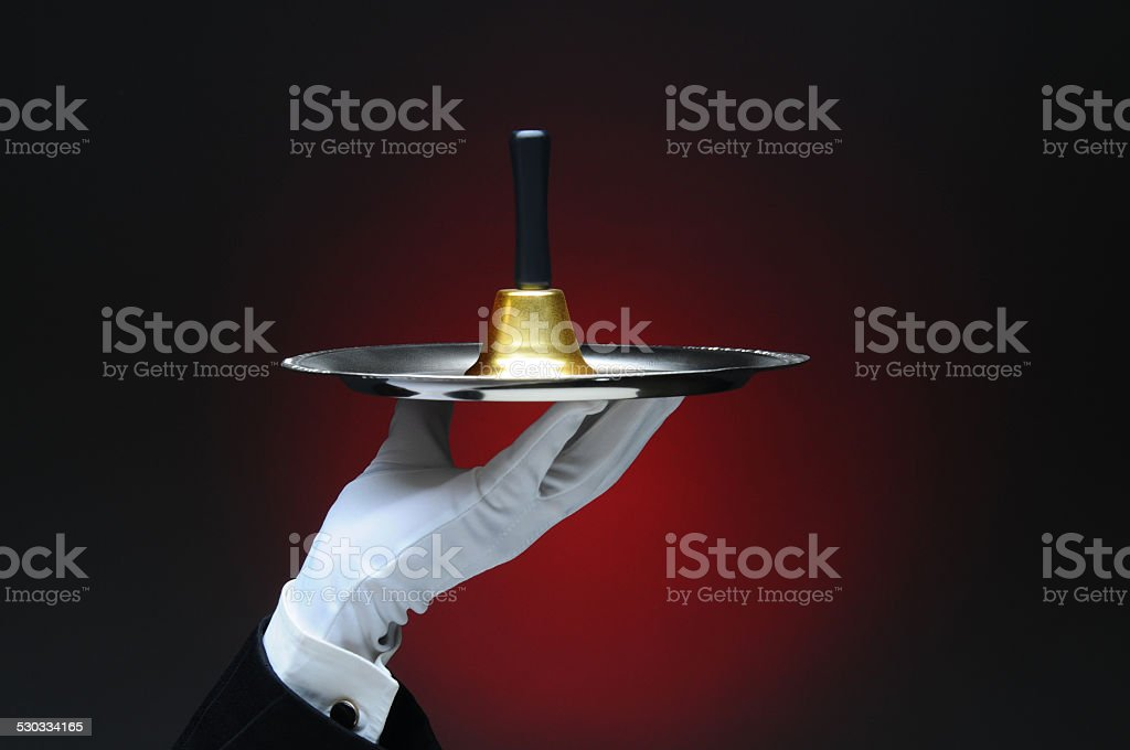 Hand Holding a Service Bell on Tray stock photo