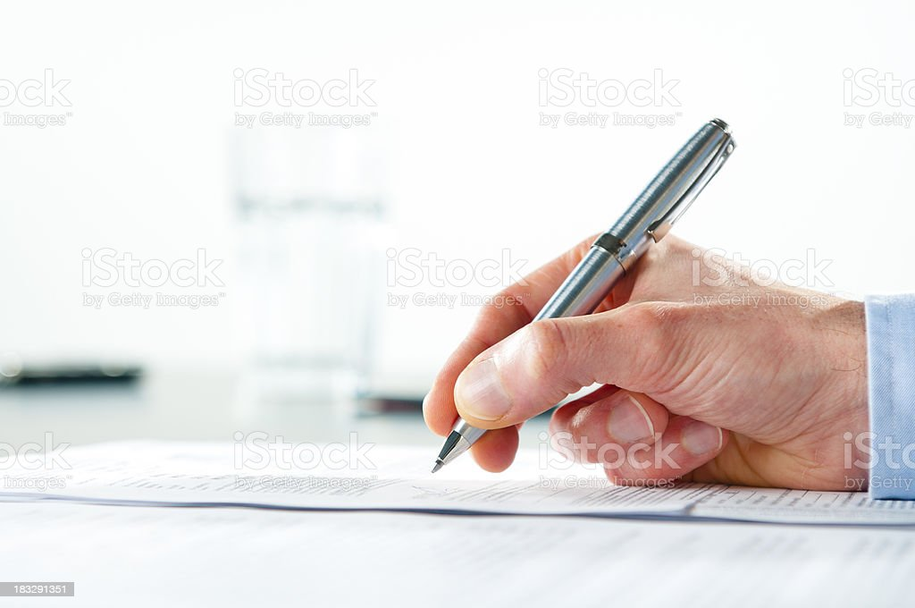 Hand holding a silver pen and signing a document stock photo