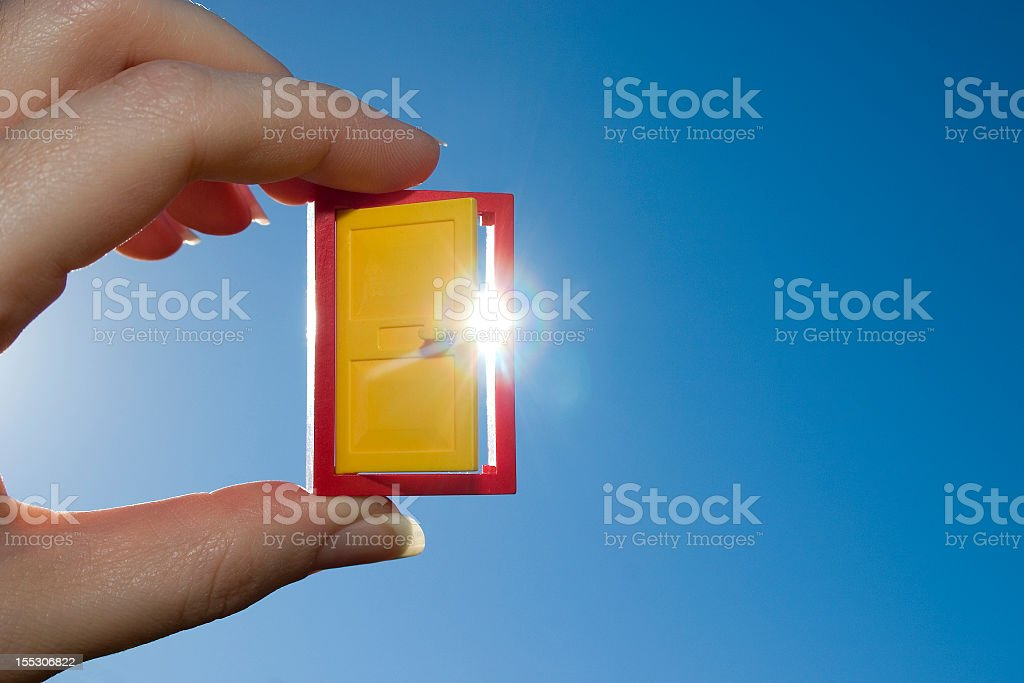 A hand holding a small yellow door of opportunity royalty-free stock photo