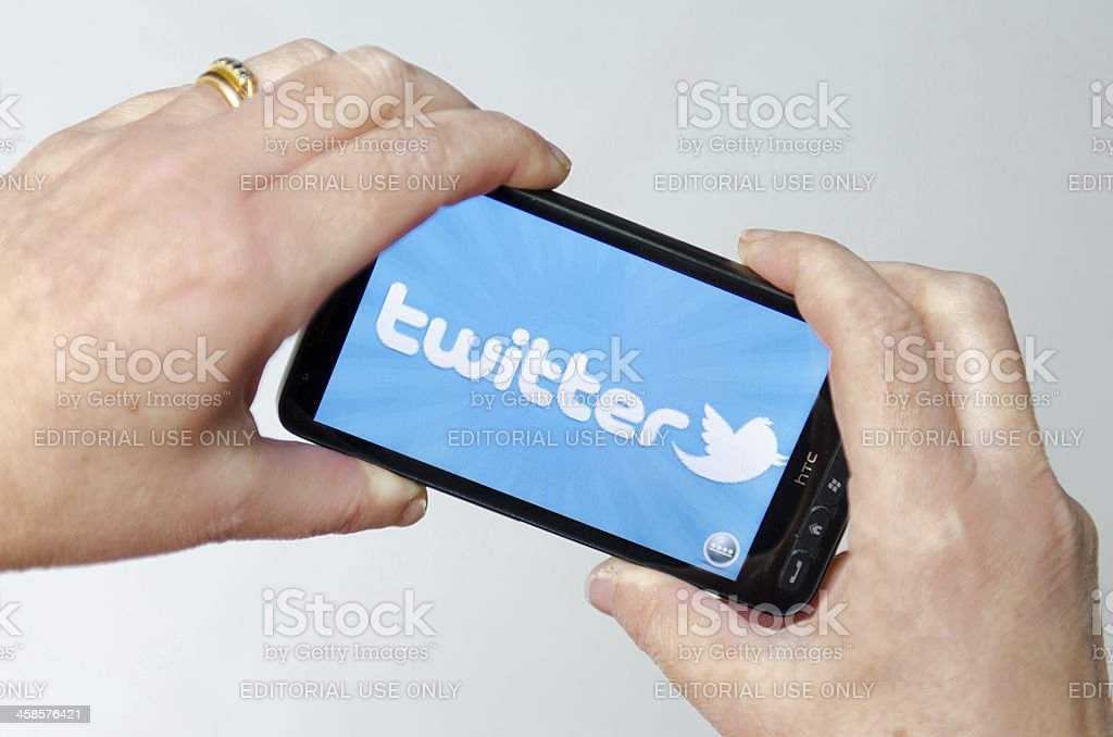 Hand holding a smarthphone showing twitter application stock photo