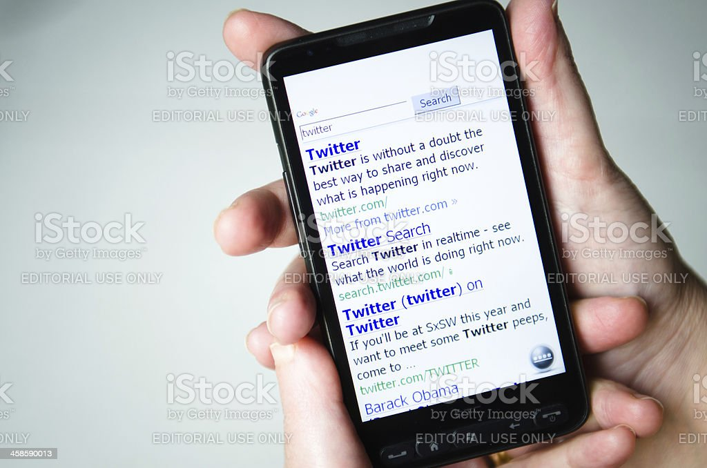 Hand holding a smarthphone showing twitter result on google stock photo