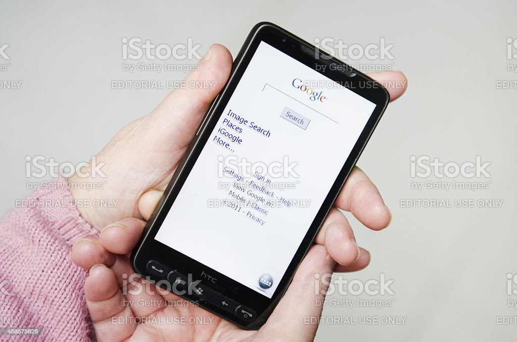 Hand holding a smarthphone with google.com apps stock photo