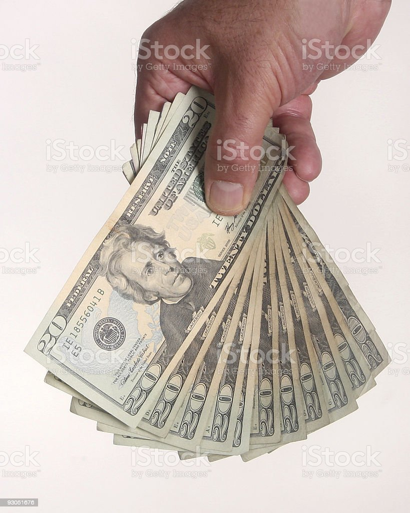 Hand holding a stack of $20 bills stock photo