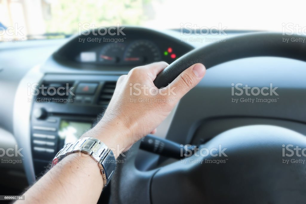 hand holding a steering wheel stock photo