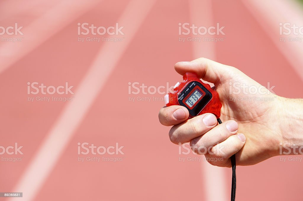 Hand holding a stopwatch on a track stock photo