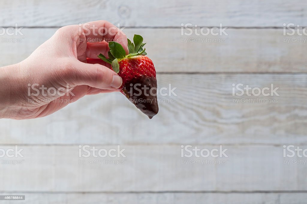 Hand holding a strawberry with chocolate stock photo