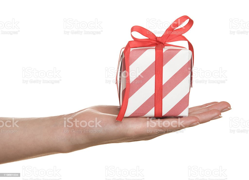 Hand holding a striped red and white gift box with bow stock photo