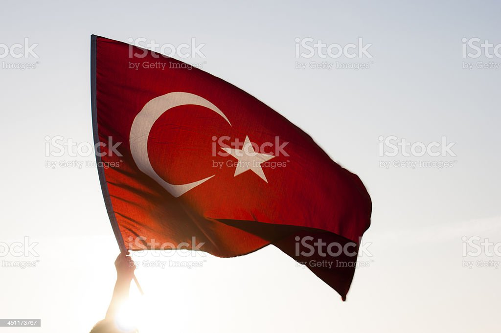 Hand holding a Turkish flag as it flies in the wind stock photo