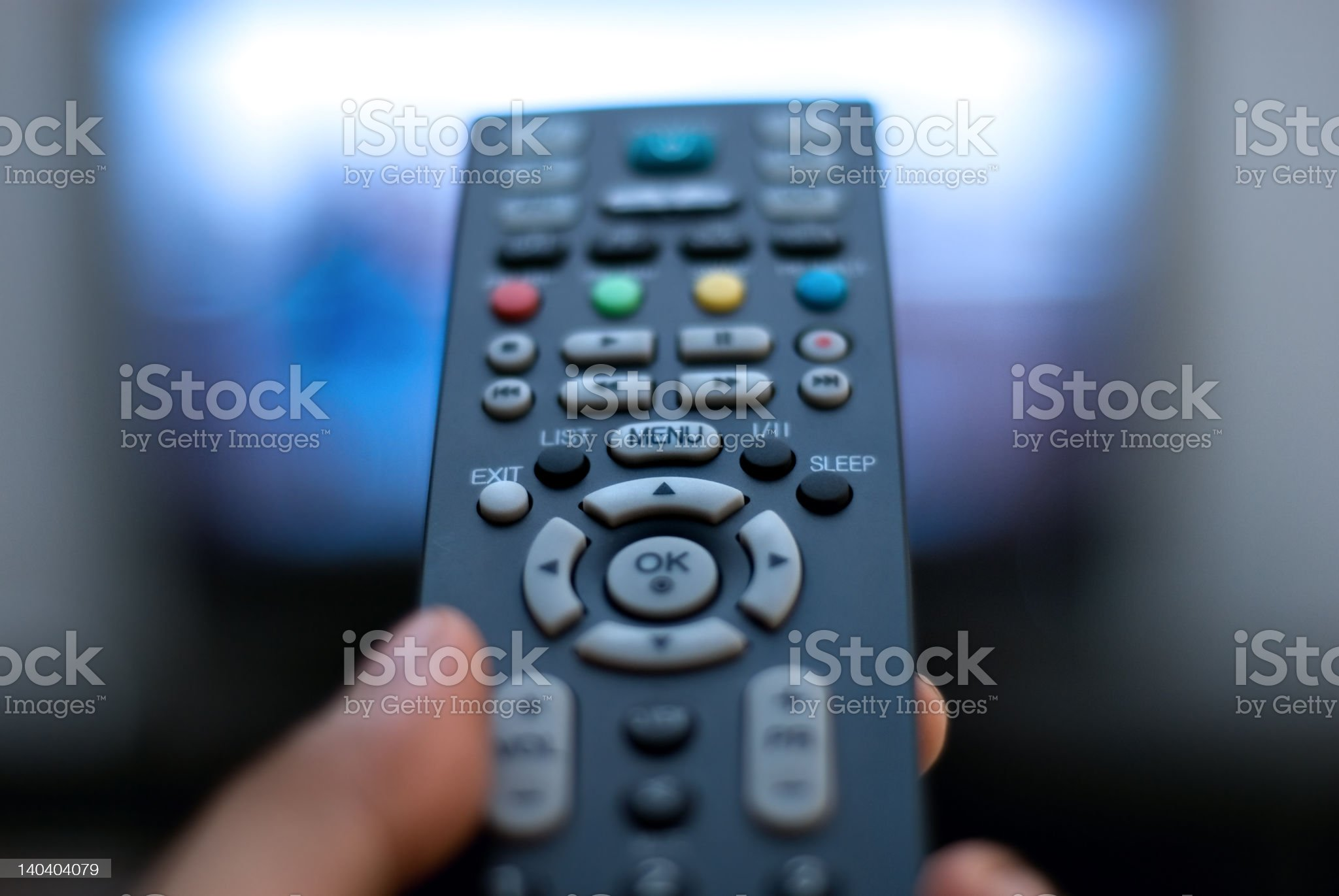 A hand holding a TV remote control royalty-free stock photo