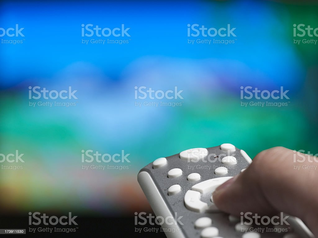 Hand holding a tv remote control stock photo