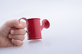 Hand holding a watering can without water on  white background