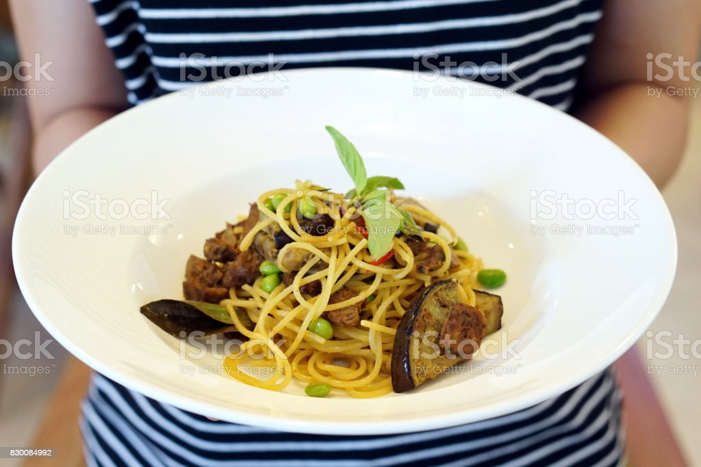 Hand holding a white plate of Green Curry Spaghetti with grilled purple eggplant (aubergine), roasted pleurotus eryngii mushroom and edamame decorated with basil, Vegetarian Food concept stock photo