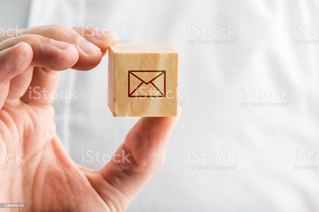 Hand holding a wooden block with an envelope icon stock photo
