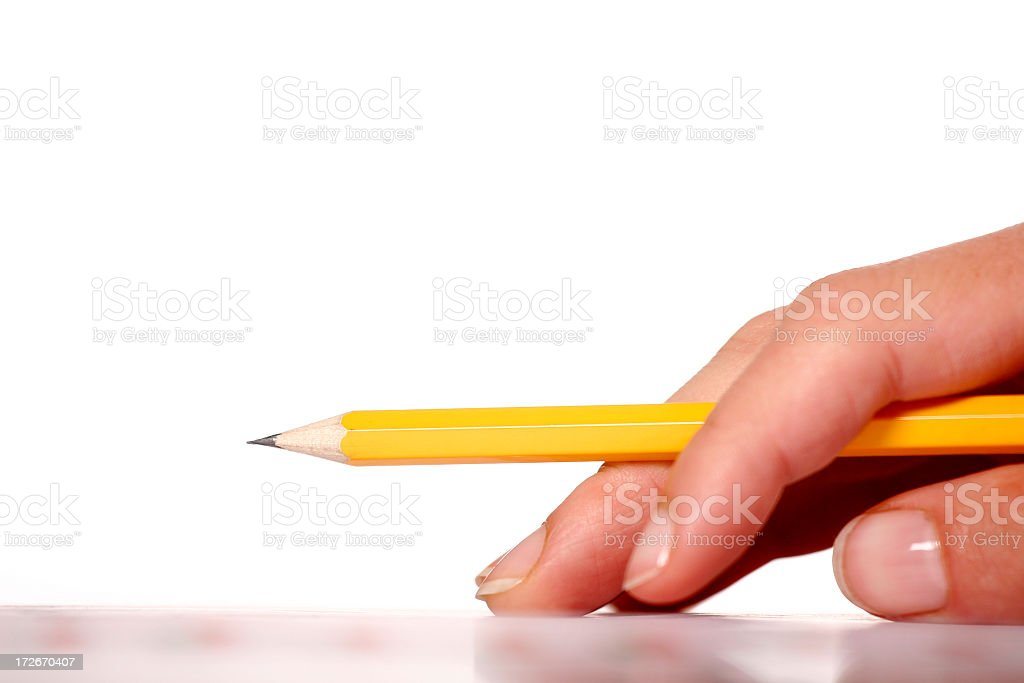 Hand holding a yellow pencil raised from a table royalty-free stock photo