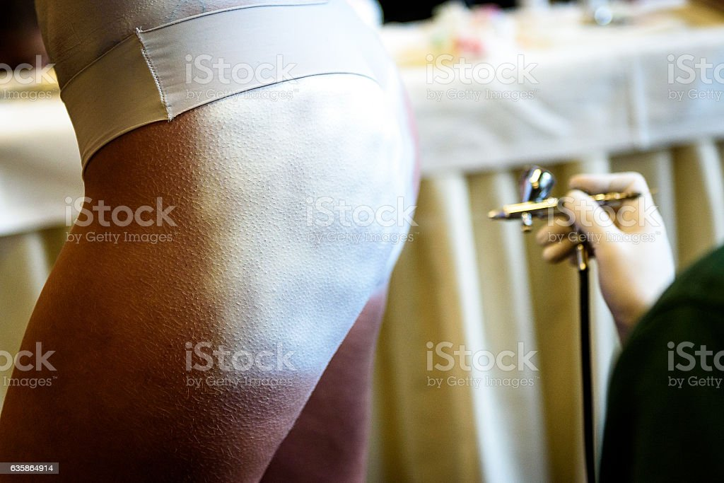 Hand holding air brush in body painting woman body. stock photo
