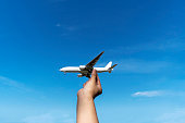 hand holding airplane in blue sky