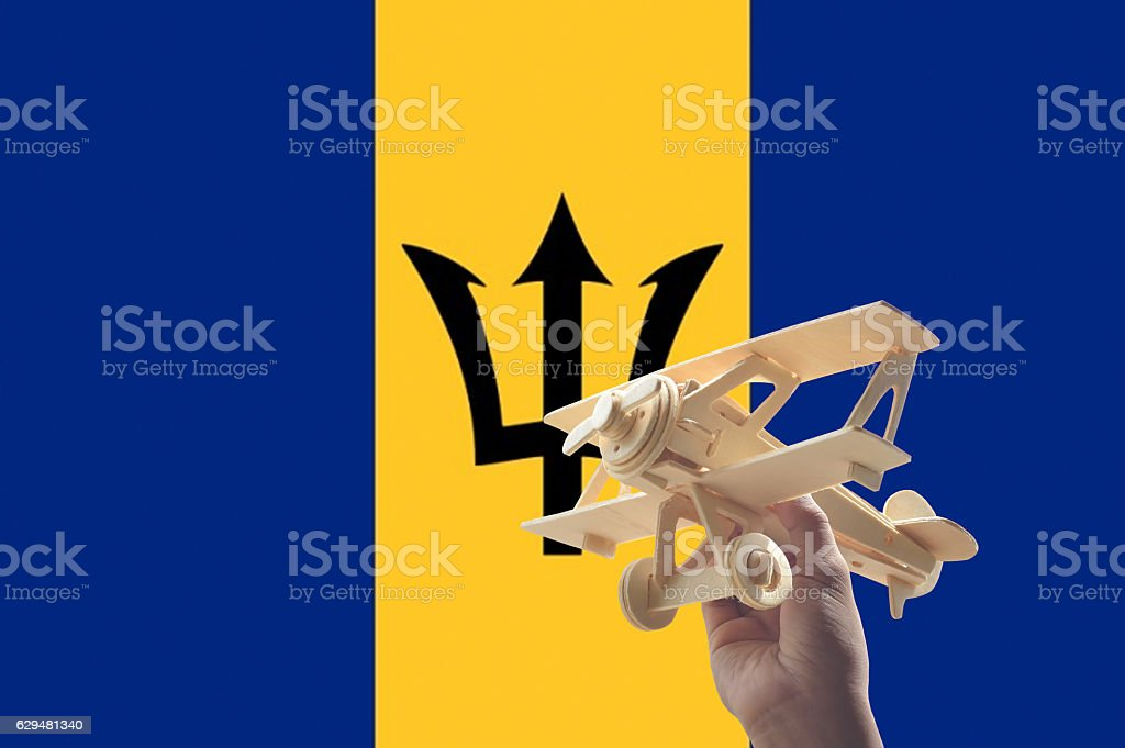 Hand holding airplane plane over Barbados flag, travel concept stock photo