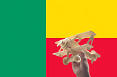 Hand holding airplane plane over Benin flag, travel concept