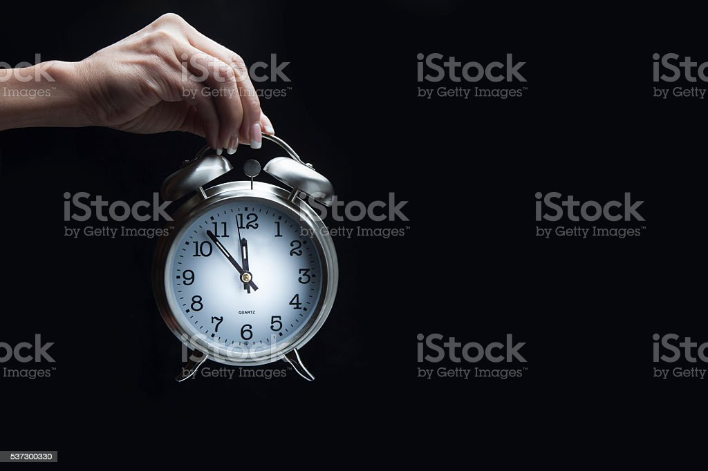 Hand holding alarm clock stock photo