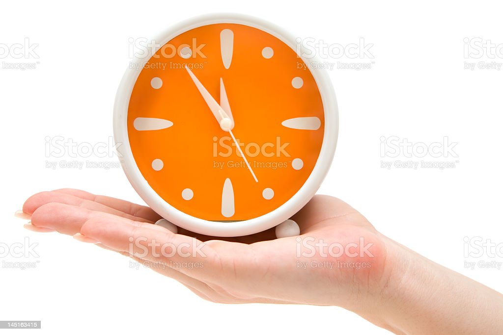 Hand holding alarm clock with orange face and white hands stock photo