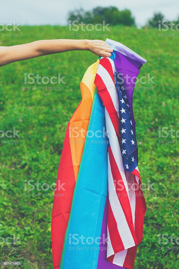 hand holding american and rainbow flag stock photo