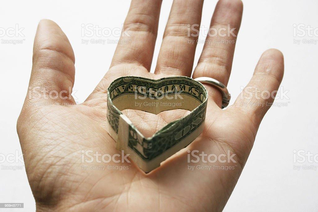 Main tenant l'Origami cœur de dollars américains photo libre de droits