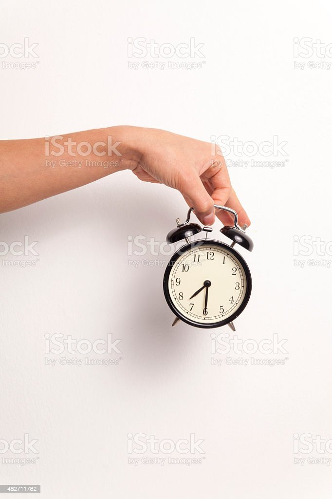Hand Holding an Alarm Clock on White Background stock photo