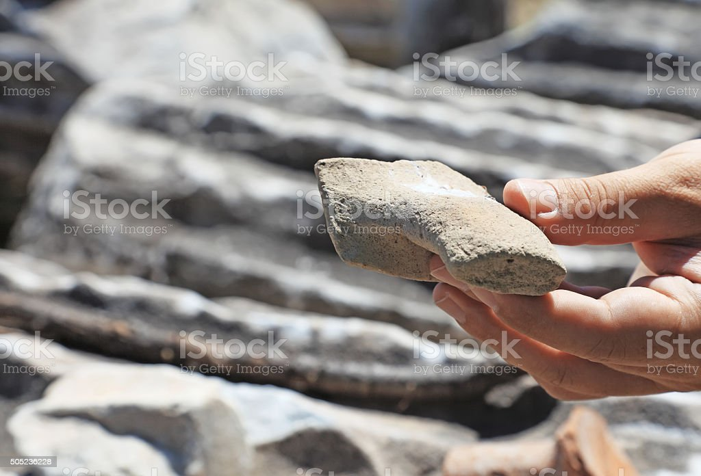 Hand holding an ancient rock stock photo